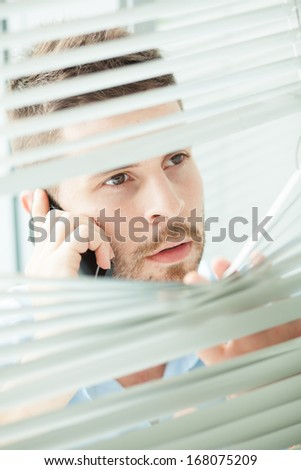 Vertical image of a businessman talking by phone while holding shutters on the foreground