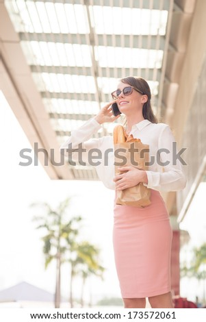vertical image of a cheerful standing with bargains and talking by phone in the store