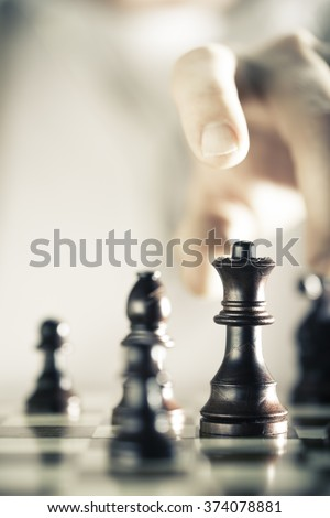Vertical Image of a chess game with focus on the queen and a blurry hand at the background, Copy space on the left side. Concept of strategic business or risk management. - stock photo