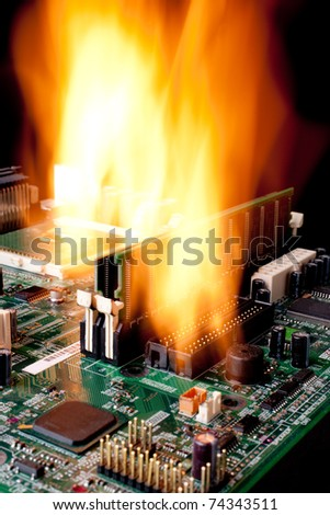 Vertical image of a computer electronic mother board on fire - stock photo