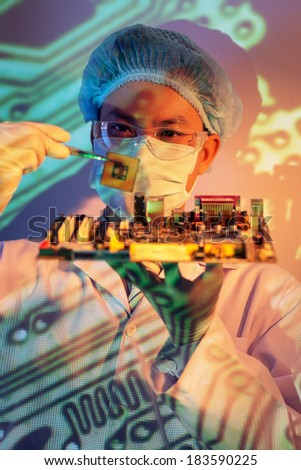 Vertical image of a concentrated it-engineer holding computer chip with tweezers on the foreground  - stock photo