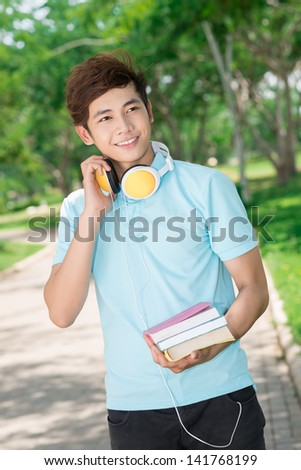 Vertical image of a cool guy with textbooks and headphones in hands - stock photo