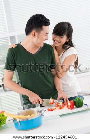 Vertical image of a couple having fun cooking together - stock photo
