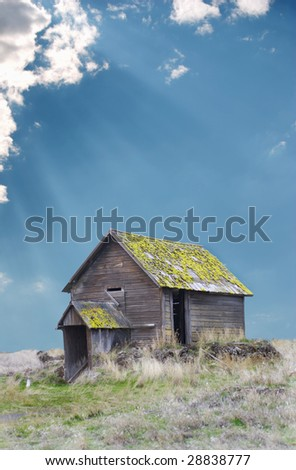 Vertical image of a derelict Eastern Oregon Homestead with sun rays shining through the clouds. - stock photo