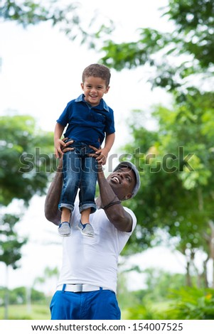 Vertical image of a father carrying his son on hands in the park and having fun - stock photo