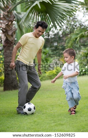 Vertical image of a father playing football with his little son on the backyard - stock photo