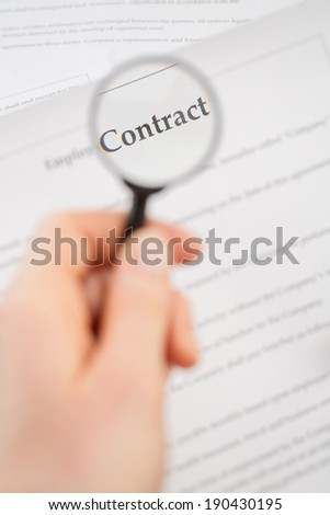 Vertical image of a female hand holding a magnifier and reading a page of a contract. - stock photo
