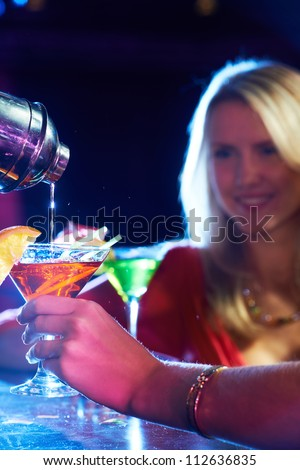 Vertical image of a female holding cocktail in martini glass - stock photo