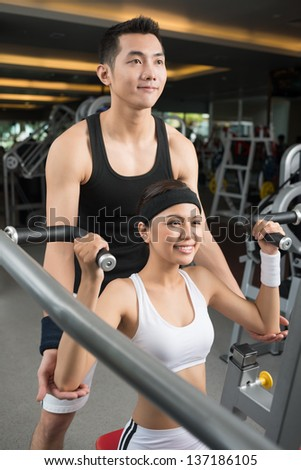 Vertical image of a fit girl exercising with her personal trainer
