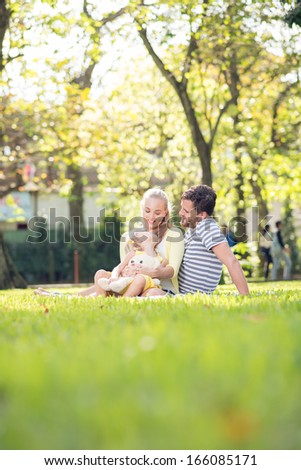 Vertical image of a happy family outdoors - stock photo