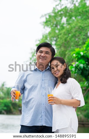 Vertical image of a happy mature couple resting outside  - stock photo