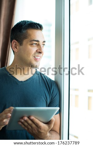 Vertical image of a man standing near the window with a tablet on the foreground - stock photo