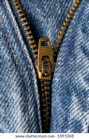 Vertical image of a partially open zipper on a pair of denim blue jeans. - stock photo