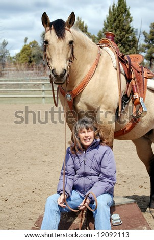Vertical image of a pretty dun quarter horse standing on a circus platform while her owner sits at her feet, smiling into the camera. - stock photo