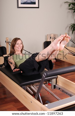 Vertical image of a professional Pilates instructor excercising on a Reformer. - stock photo