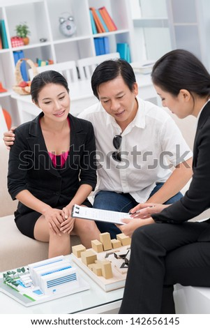 Vertical image of a realtor presenting different variants to her clients - stock photo