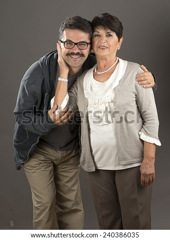 Vertical image of a senior adult woman and her son over gray background. - stock photo