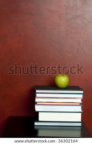 Vertical image of a stack of books with a green apple - stock photo