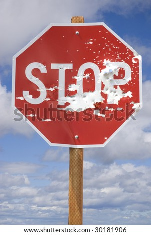 Vertical image of a stop sign shot full of bullet holes against a blue, cloudy sky.