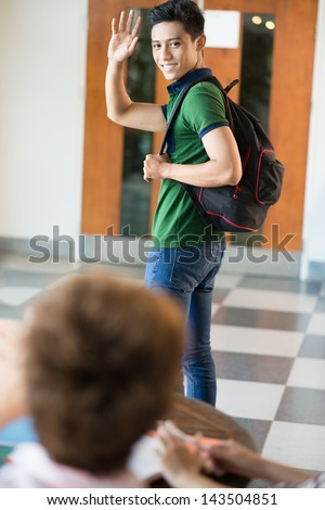 Vertical image of a student saying 'bye'?� to his fellow-student - stock photo