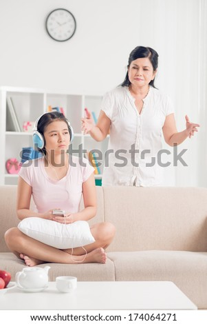 Vertical image of a teenager I differently listening to the music in headphones while her mother addressing to her on the foreground  - stock photo
