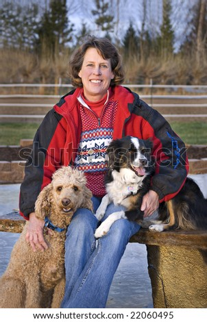 Vertical image of a woman sitting outdoors with her Standard Poodle and Miniature Australian Shepherd. Focus on woman's face. - stock photo