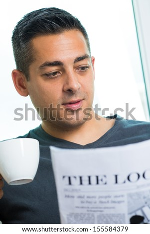 Vertical image of a young man with a teacup reading the newspaper - stock photo