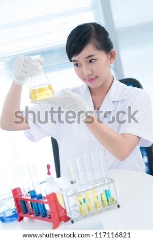 Vertical image of a young woman studying substance in a flask - stock photo