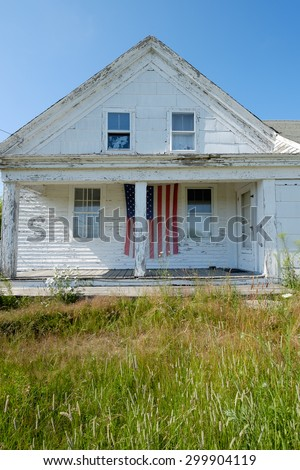 Vertical image of an old abandoned farmhouse with an american flag on the large empty abandoned veranda porch  - stock photo