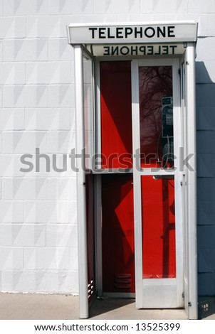 Vertical image of an old, still operational telephone booth.  The booth background is dark red in color and stands against a light colored wall. - stock photo