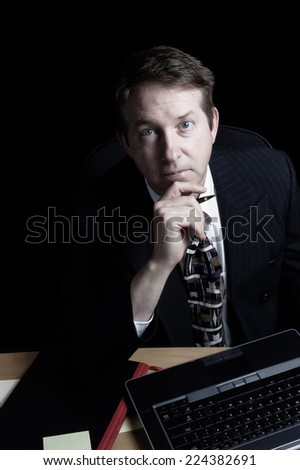Vertical image of business man, looking forward, working late with black background  - stock photo