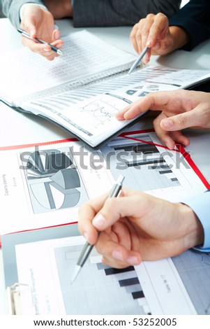 Vertical image of business partners hands over papers discussing them - stock photo