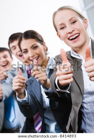 Vertical image of business people giving the thumbs-up sign - stock photo
