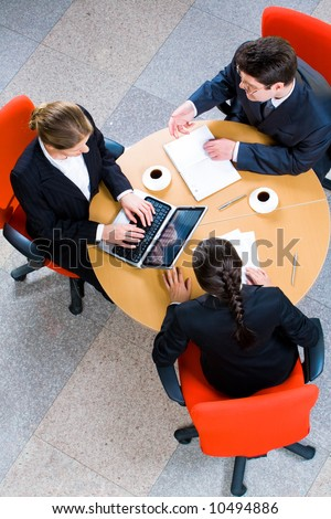 Vertical image of business people working at meeting - stock photo