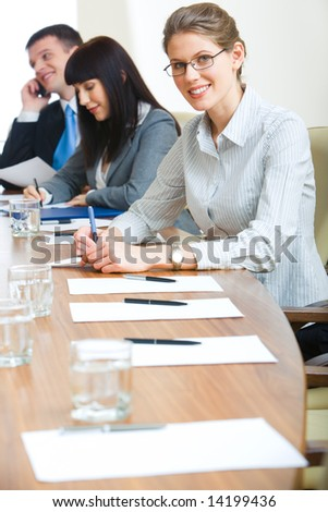 Vertical image of business persons sitting at the table at seminar - stock photo