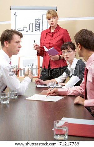 Vertical image of business team talking during meeting while confident man explaining something - stock photo