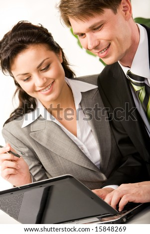 Vertical image of businessman and businesswoman doing some computer work together