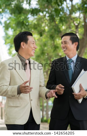 Vertical image of businesspeople discussing something walking in the park - stock photo