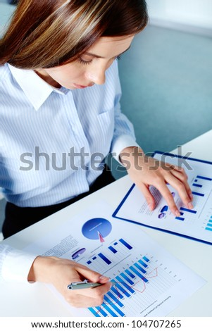 Vertical image of businesswoman working with financial document - stock photo