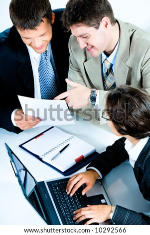 Vertical image of busy teamwork from above: two businessmen discussing business plan while business lady typing document on the laptop