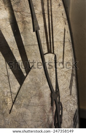 Vertical image of clock showing 5 to midnight with rough texture - stock photo