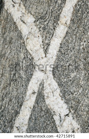 vertical image of crossing rock veins in an x shape - stock photo