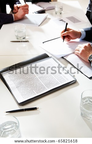 Vertical image of document at workplace with human hands during business discussion on background - stock photo