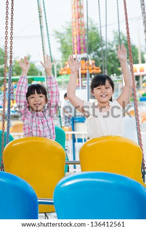 Vertical image of female youngsters sitting on swings with their hands raised - stock photo