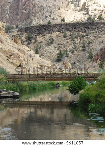 vertical image of footbridge over the crooked river, Smith Rock State Park, Oregon - stock photo