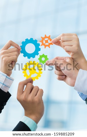 Vertical image of human hands holding gear mechanism in sign of cooperation  - stock photo