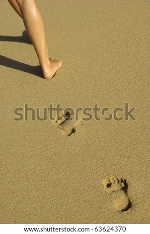 Vertical image of lady footprints on the beach. - stock photo