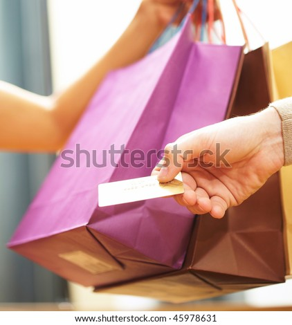 Vertical image of man?s hand passing over credit card to shop assistant after shopping - stock photo