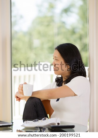 Vertical image of mature woman relaxing while working from home with bright daylight coming in from window in background - stock photo