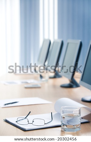 Vertical image of notepad with eye glasses on it and glass of water near by